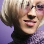Portrait of smiling blond young adult Caucasian woman on purple background wearing sunglasses and scarf.